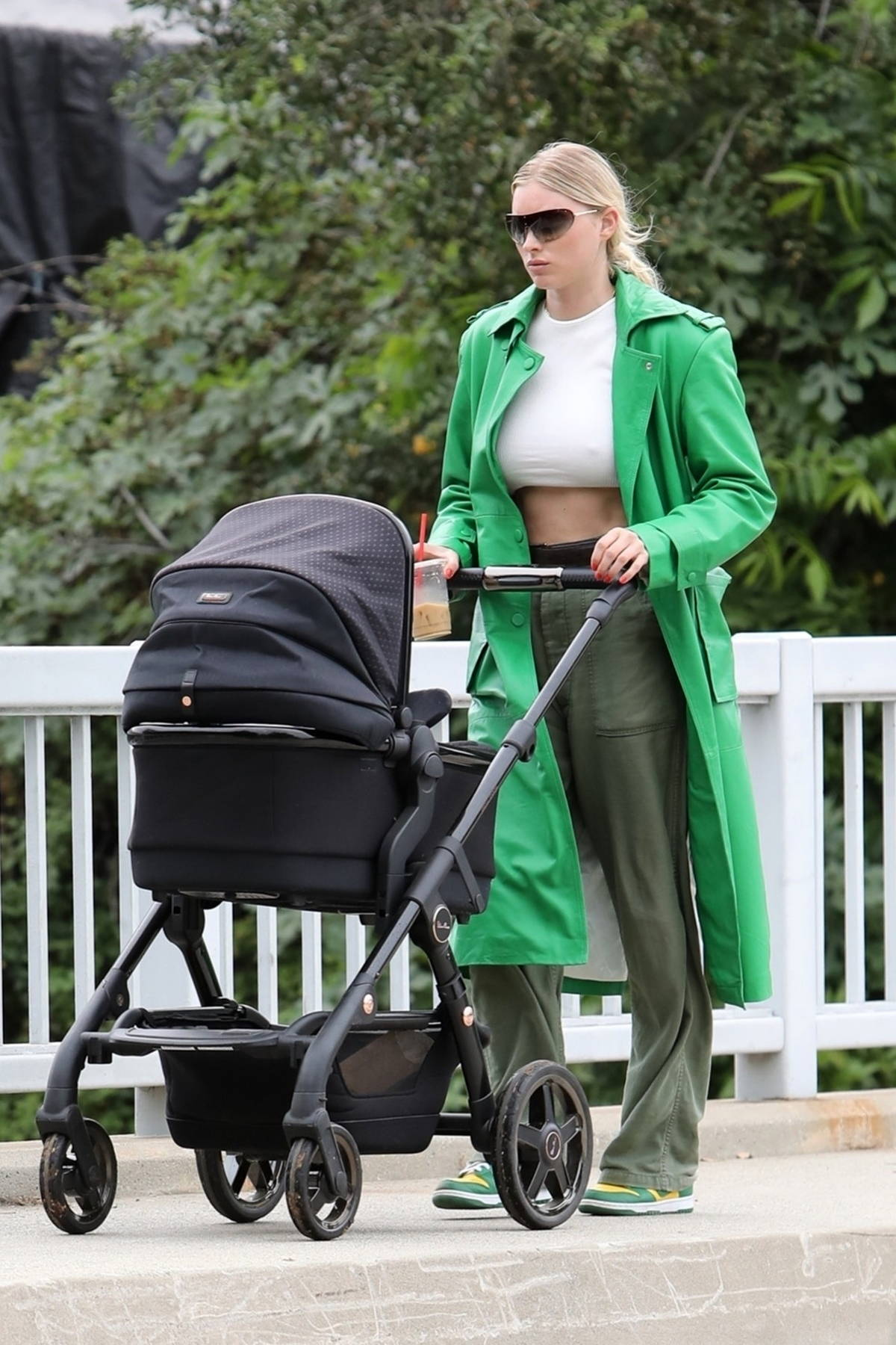 Elsa Hosk wears a midriff baring crop top and a green trench coat during a coffee run with her baby daughter in Los Angeles