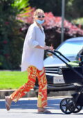 Elsa Hosk wears an oversized shirt and patterned orange pants while heading out for coffee with her daughter in Los Angeles