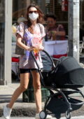 Emily Ratajkowski wears a printed tee and black legging shorts while out for a stroll with her baby in SoHo, New York City