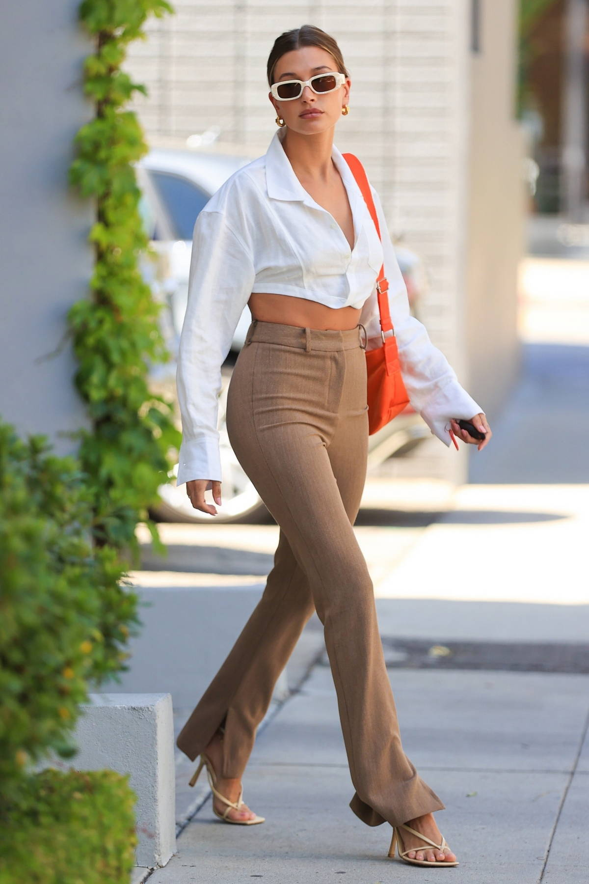 Hailey Bieber looks chic in a cropped white shirt with brown trousers while attending a business meeting in Los Angeles