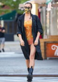 Irina Shayk looks gorgeous in an orange mini dress with a black jacket and leather boots while running errands in New York City