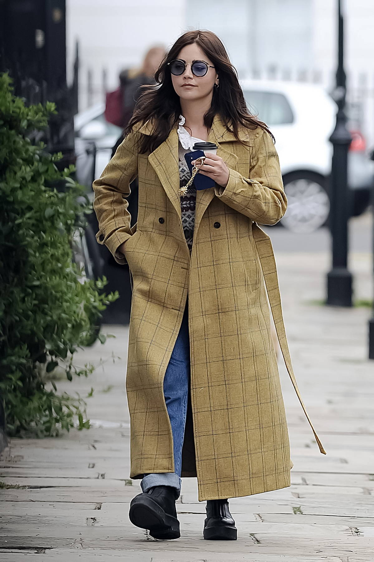 Jenna Coleman wears a checkered trench coat while stepping out for coffee in London, UK