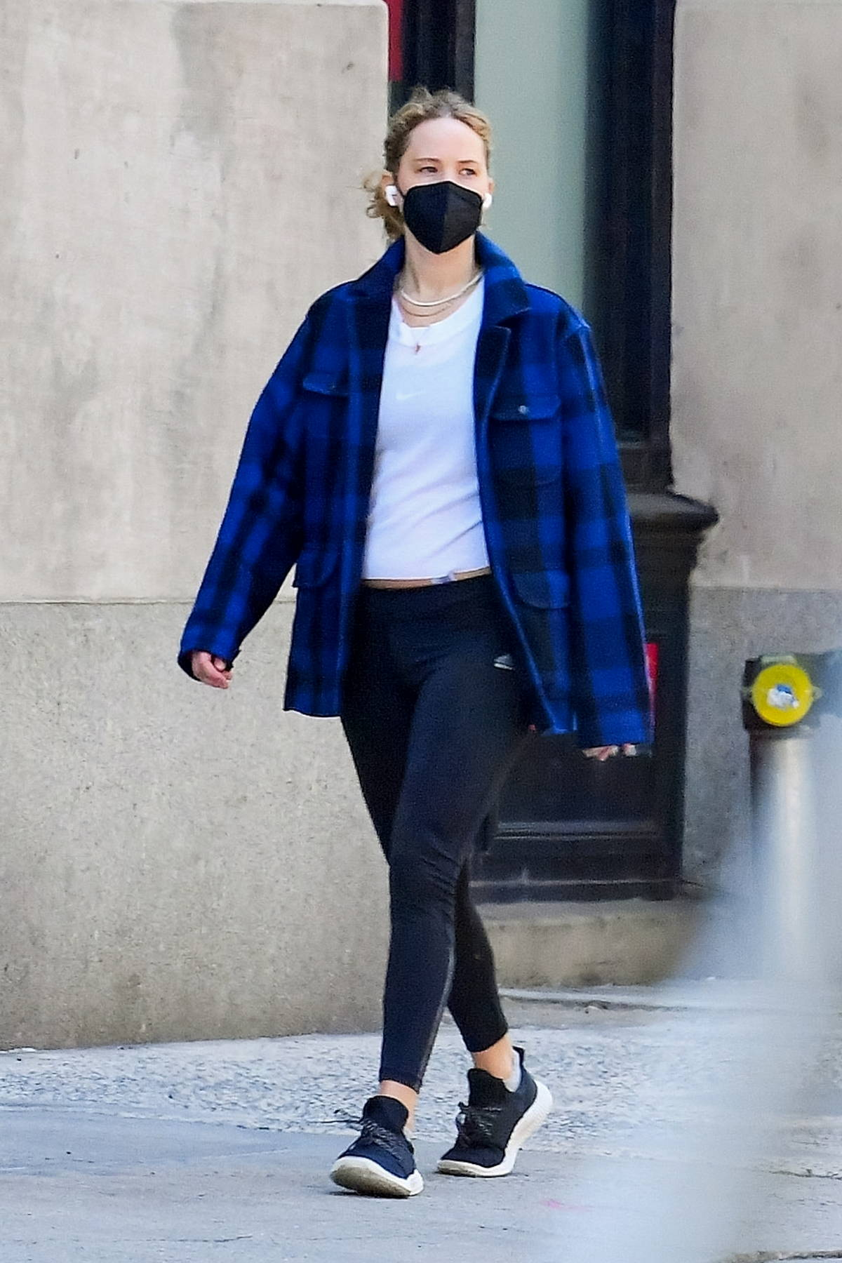 Jennifer Lawrence wears a blue flannel shirt, a white tee and black leggings as she steps out in Tribeca, New York