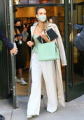 Jessica Alba dons a pastel green top with matching handbag as she greets her fans while leaving her hotel in New York City