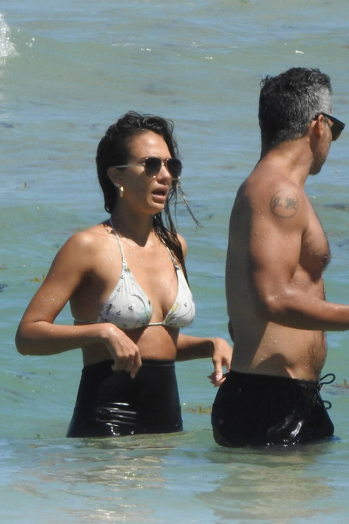 Jessica Alba wears a bikini top and legging shorts as she takes a dip into the ocean in Miami, Florida