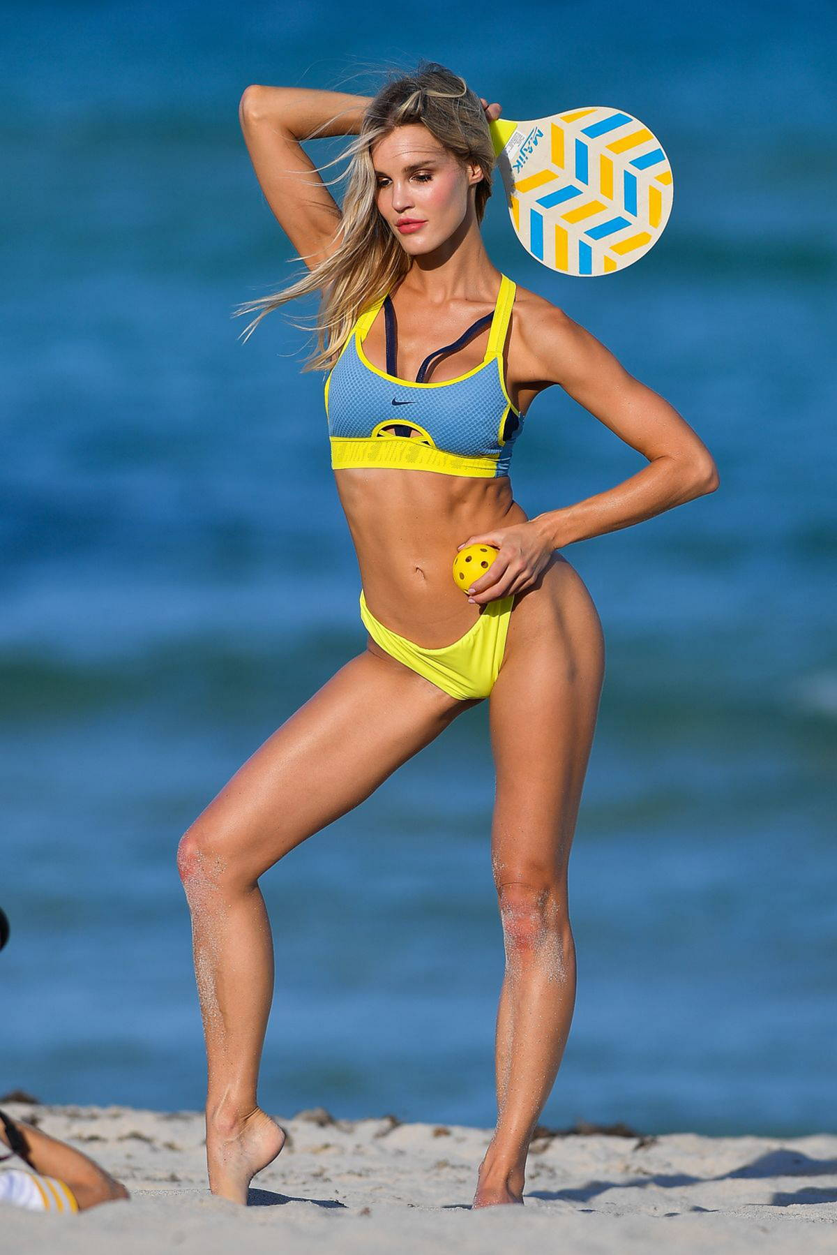 Joy Corrigan poses in a bright yellow and blue Nike bikini for a beach photoshoot in Miami Beach, Florida