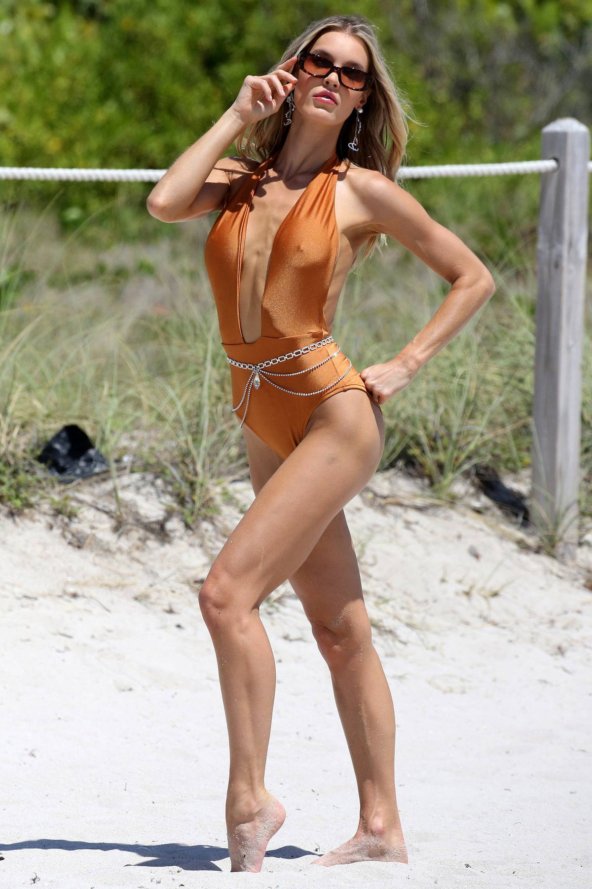 Joy Corrigan shows off her beach body while posing in a gold swimsuit during a photoshoot in Miami Beach, Florida