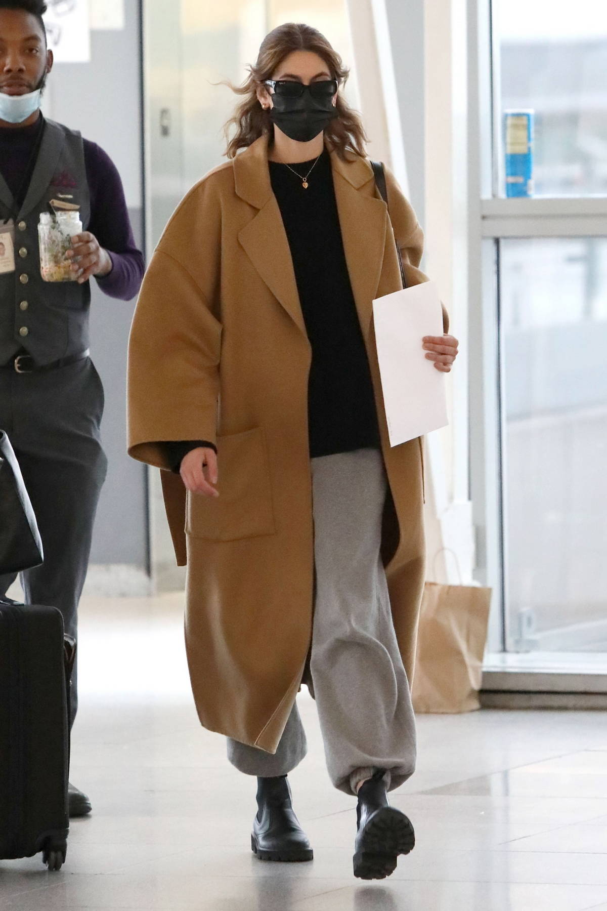 Kaia Gerber bundles up in a brown trench coat as she arrives at JFK Airport for a flight out of New York