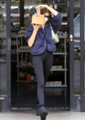 Kaia Gerber showcases her model legs in black leggings while grabbing juice at the Earth Bar in West Hollywood, California