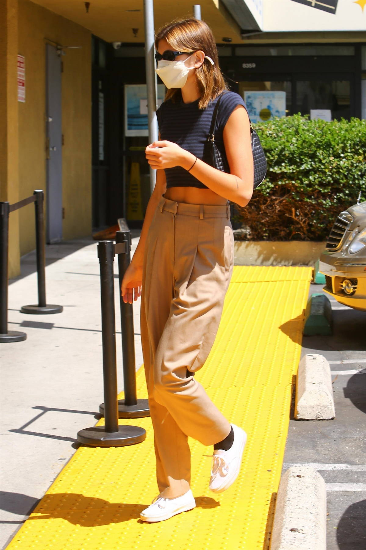 Kaia Gerber wears a black crop top and brown pleated trousers while stopping by the Earth Bar in West Hollywood, California