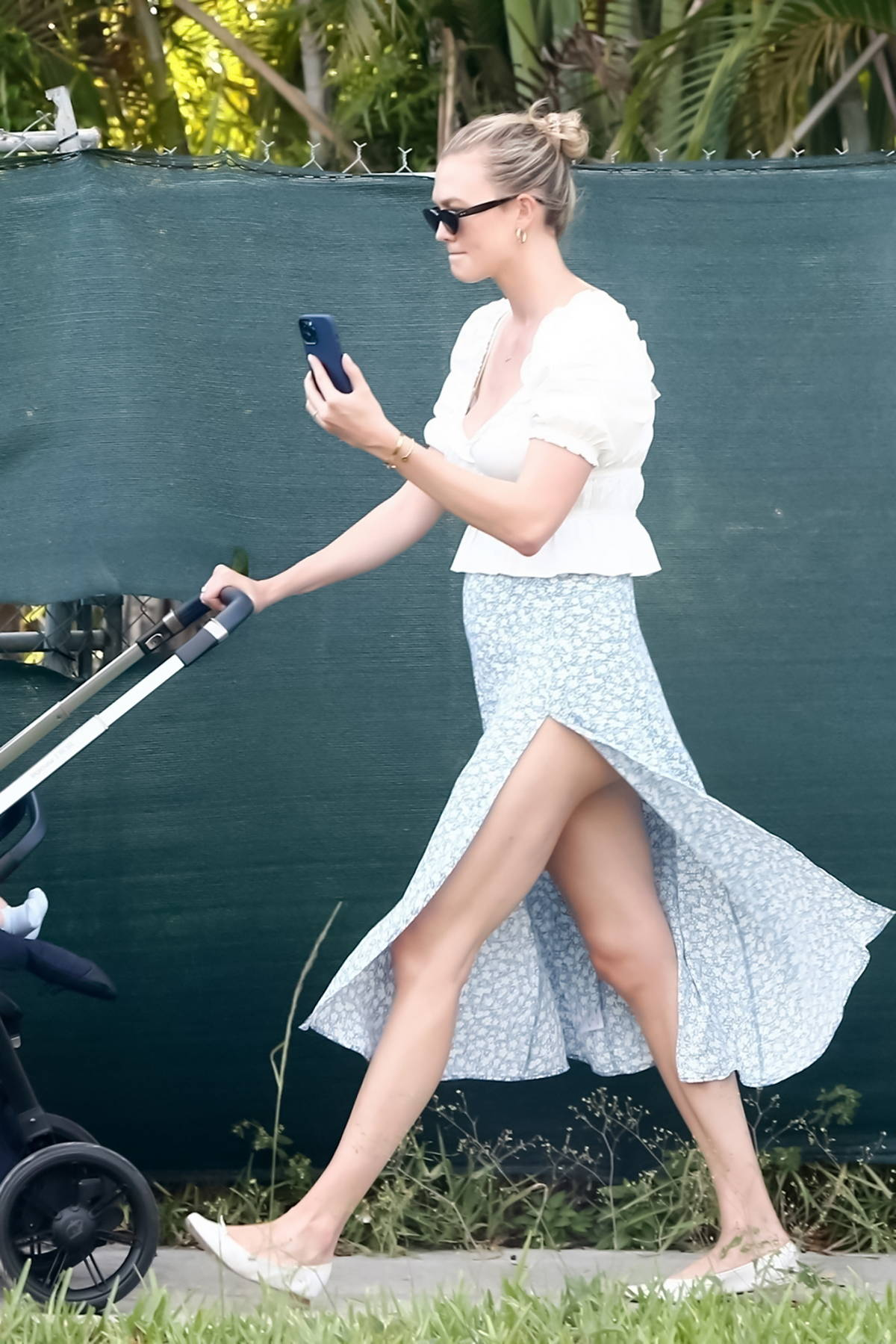 Karlie Kloss wears a white top and floral print skirt while out for an afternoon walk with her son in Miami, Florida