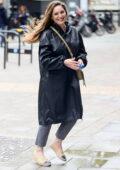 Kelly Brook braves the rain in a waterproof raincoat outside the Heart Radio in London, UK