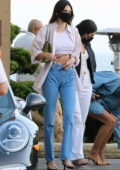 Kendall Jenner shows off her slim waistline in a white crop during a dinner outing with friends at Nobu in Malibu, California