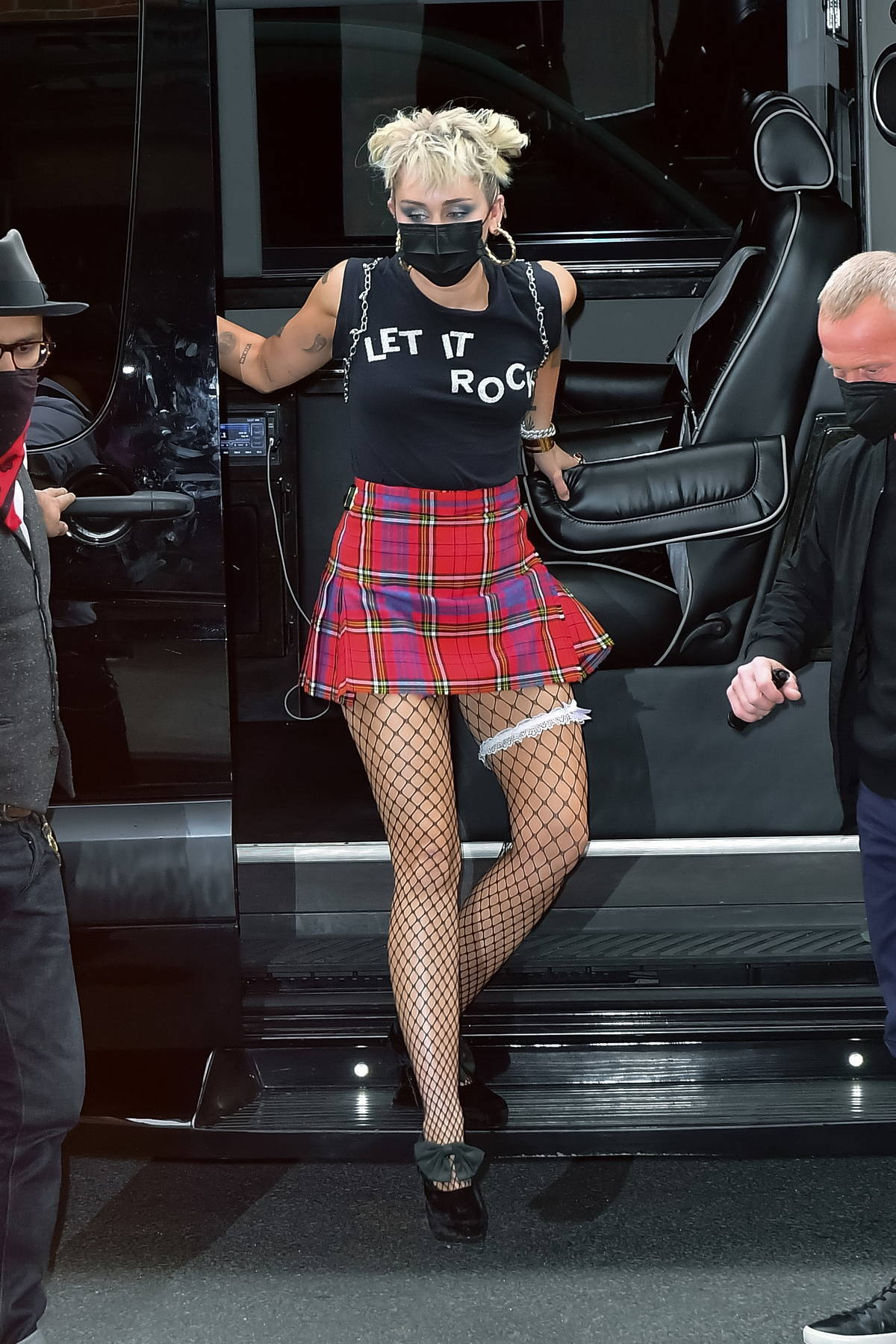 Miley Cyrus rocks a tartan mini skirt with fishnet as she arrives back to her hotel after rehearsing for SNL in New York City