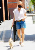 Naomi Watts wears a sheer white top and denim shorts while walking her dog in New York City