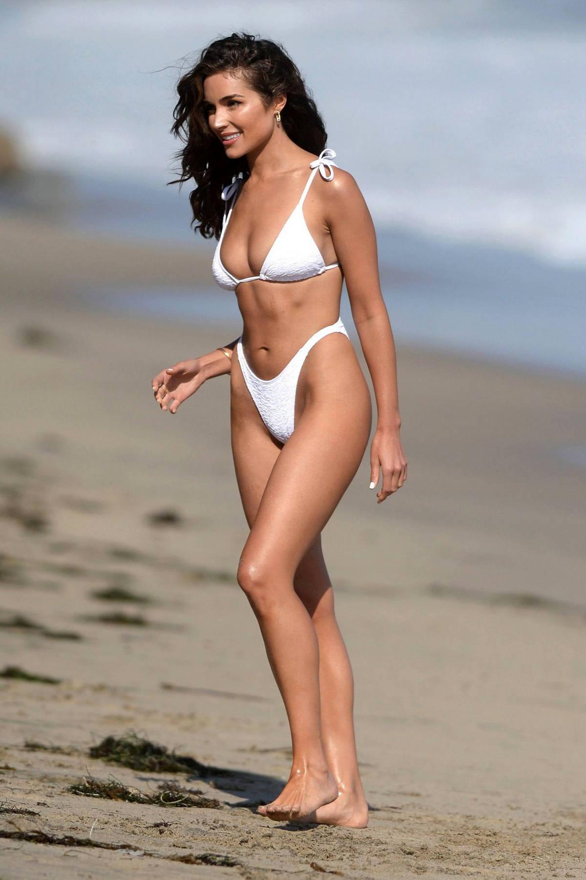 Olivia Culpo looks stunning in a white bikini while enjoying the beach with her pup in in Malibu, California