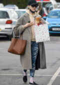 Phoebe Dynevor bundles up in a tweed coat with a hoodie and leggings as she grabs an iced-coffee while out in Manchester, UK