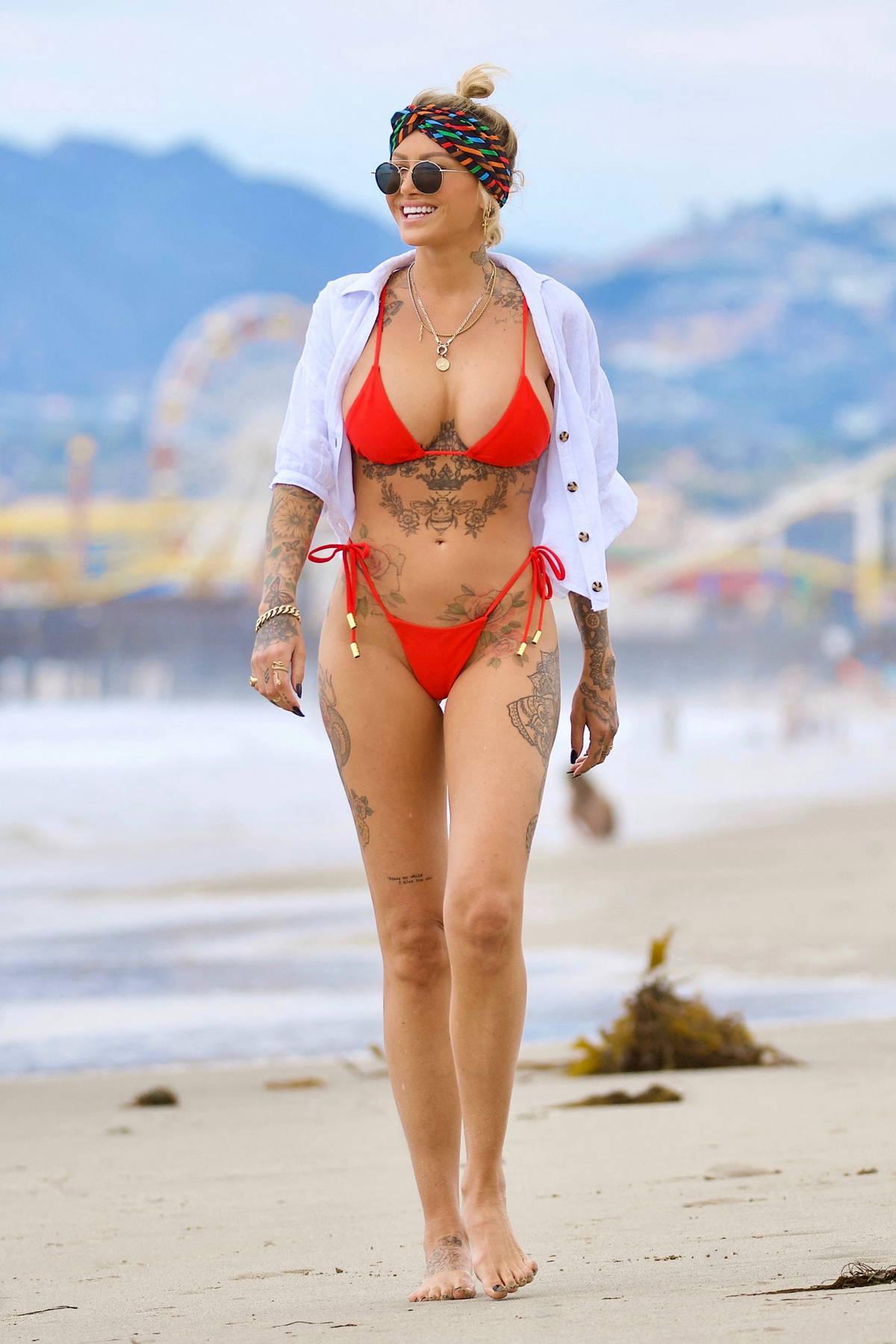 Tina Louise sizzles in a red bikini while enjoying a beach day with new boyfriend Brett Oppenheim in Venice Beach, California