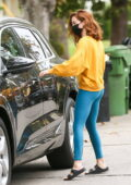 Zoey Deutch sports a bright yellow sweatshirt and aqua leggings while leaving her house in Los Angeles
