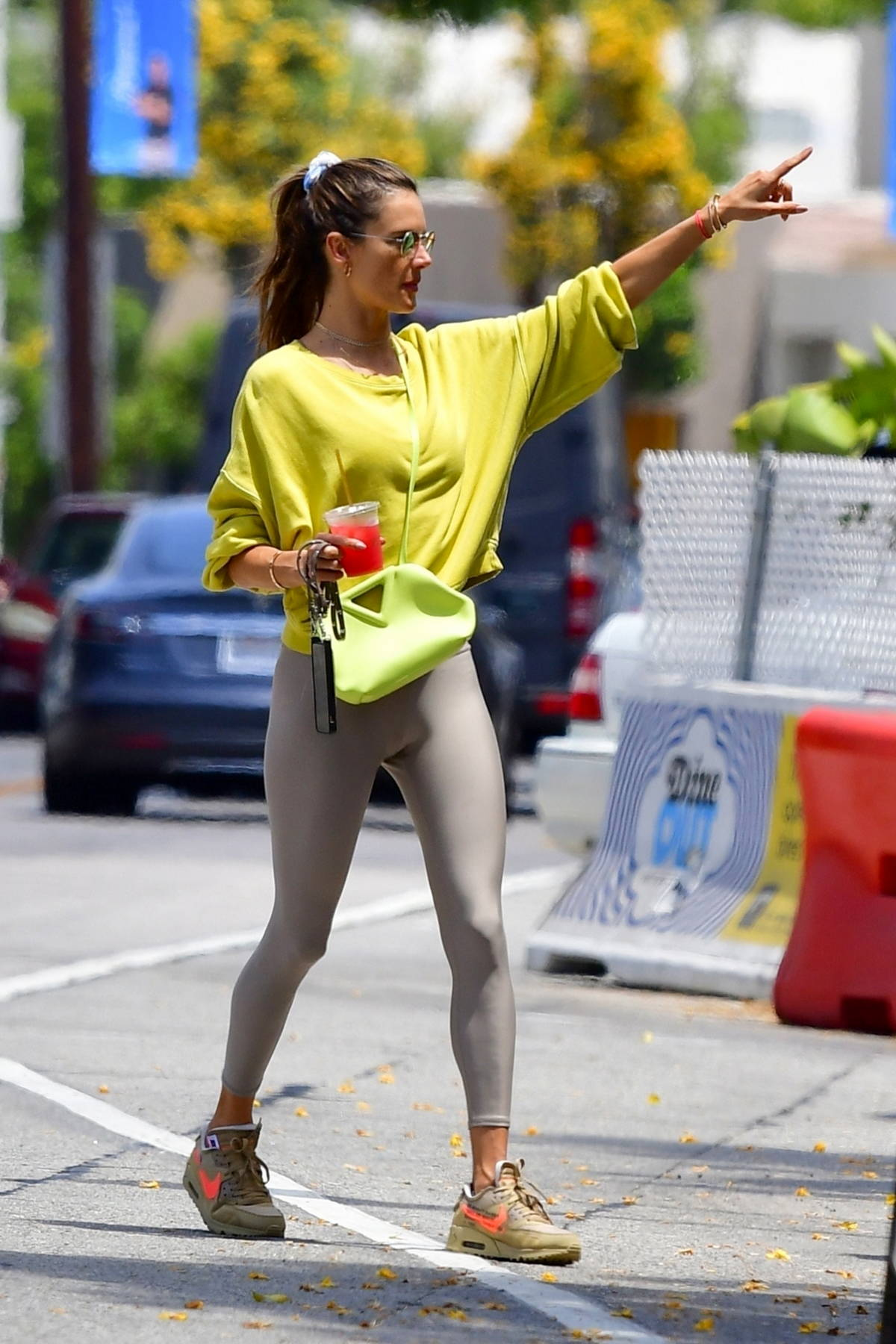 Alessandra Ambrosio enjoys a cold drink while out for lunch with a friend in Beverly Hills, California
