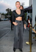 Alexis Ren flaunts her tiny waistline in a black crop top and denim while out for dinner at Catch in West Hollywood, California