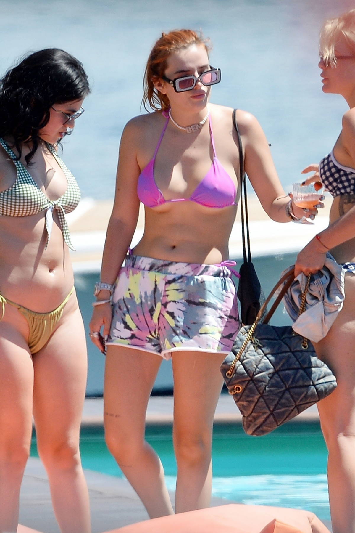 Bella Thorne wears a bikini top and shorts while relaxing by the pool with friends in Como, Italy