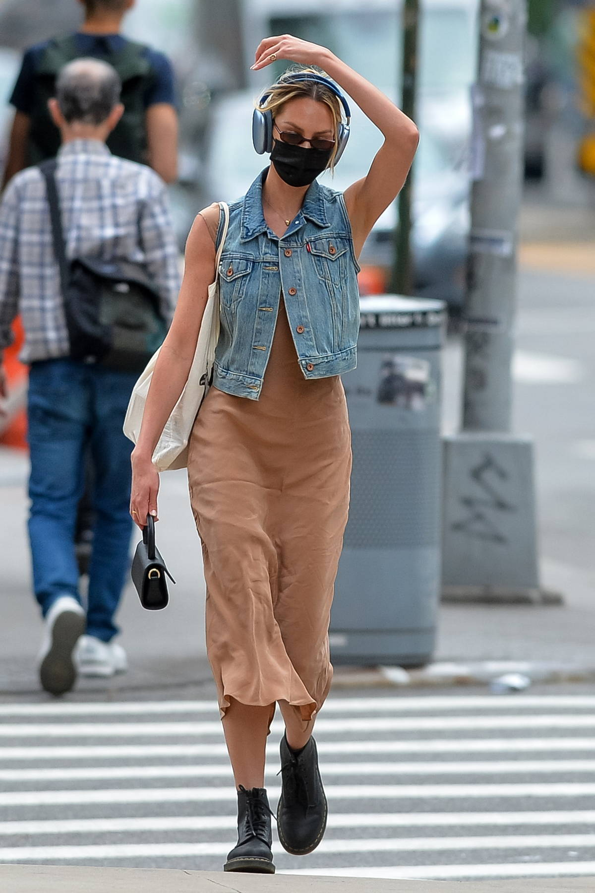 Candice Swanepoel dons a beige dress and blue denim vest with matching headphones while out in New York City