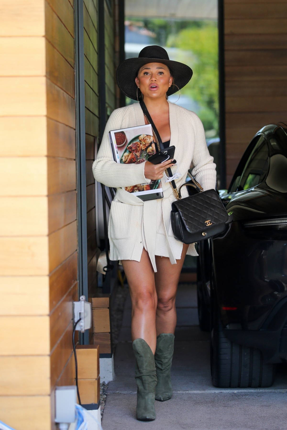 Chrissy Teigen flaunts her legs in denim shorts as she as she arrives at her office in Los Angeles