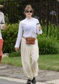 Elizabeth Olsen wears a semi-sheer white top and cream harem pants during a coffee run with Robbie Arnett in Studio City, California