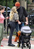Emma Roberts and Garrett Hedlund share a kiss while out for a stroll with their baby in Boston, Massachusetts