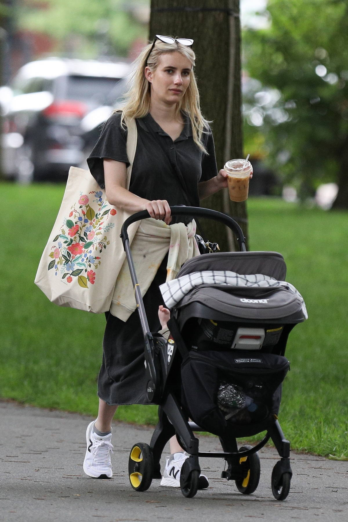 Emma Roberts enjoys an iced coffee while out on a morning walk with her baby in Boston, Massachusetts
