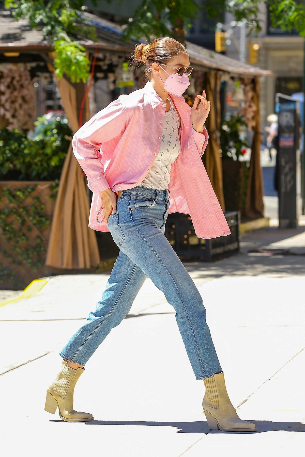 Gigi Hadid looks fab in an unbuttoned pink shirt and blue jeans as she arrives back at her apartment in New York City