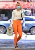 Hailey Bieber rocks a pair of bright orange leggings and sneakers while visiting a doctor's office in Beverly Hills, California