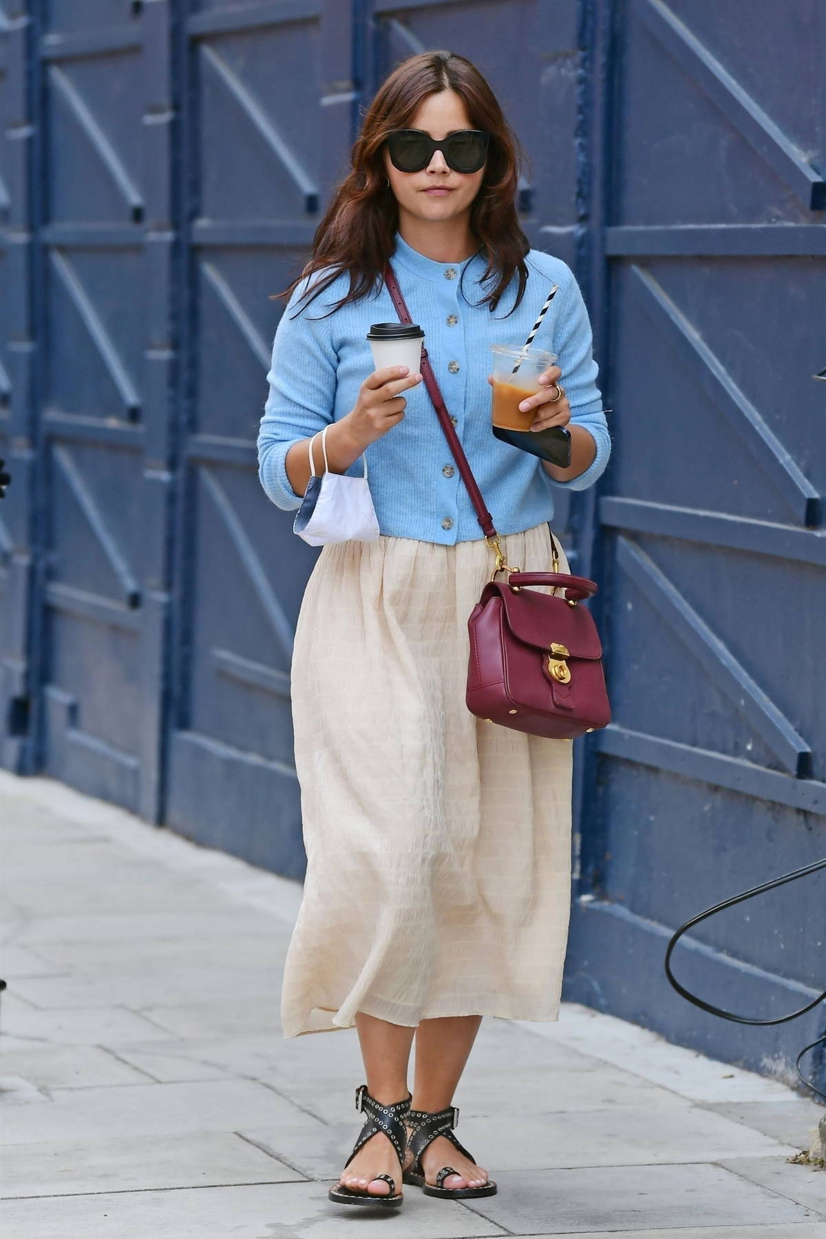 Jenna Coleman wears a pastel blue top and cream skirt while making a coffee run in London, UK