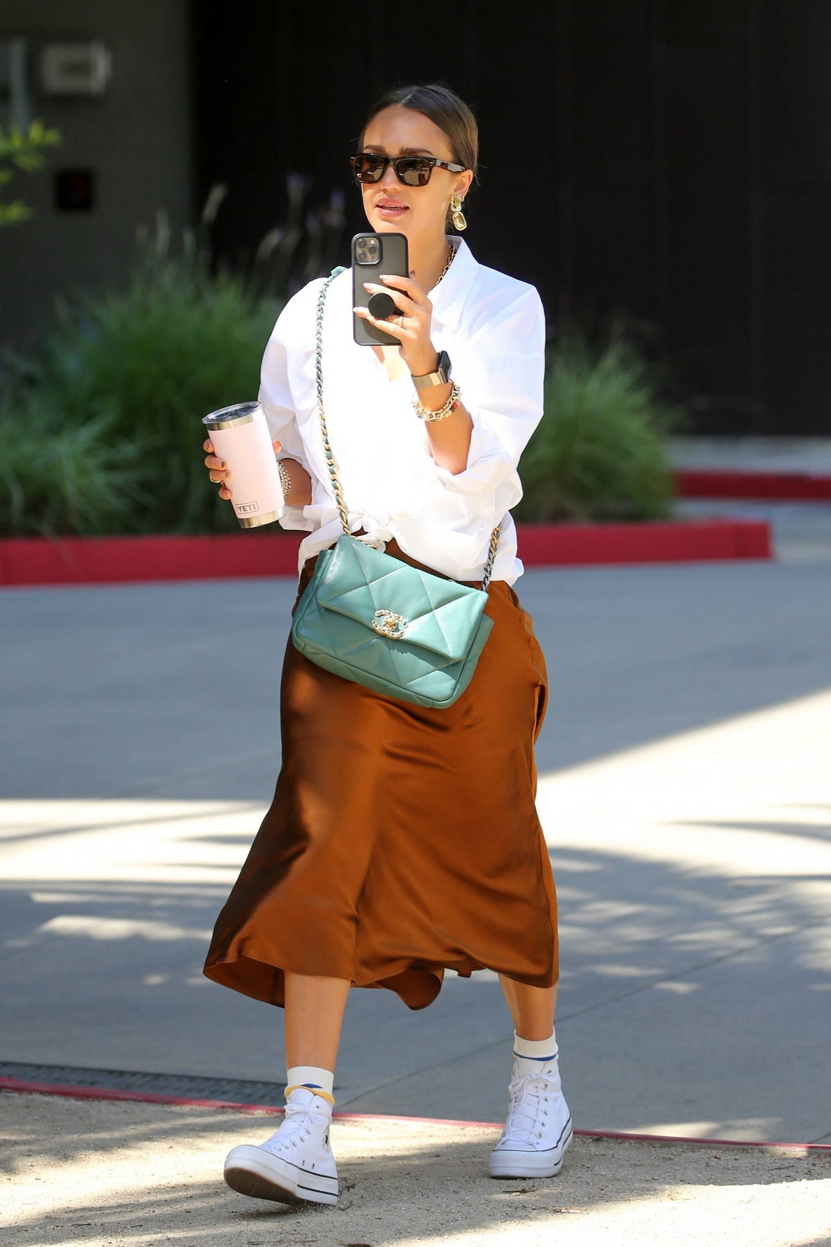 Jessica Alba looks great in a white blouse and burnt orange skirt while arriving at Honest Company Headquarters in Los Angeles