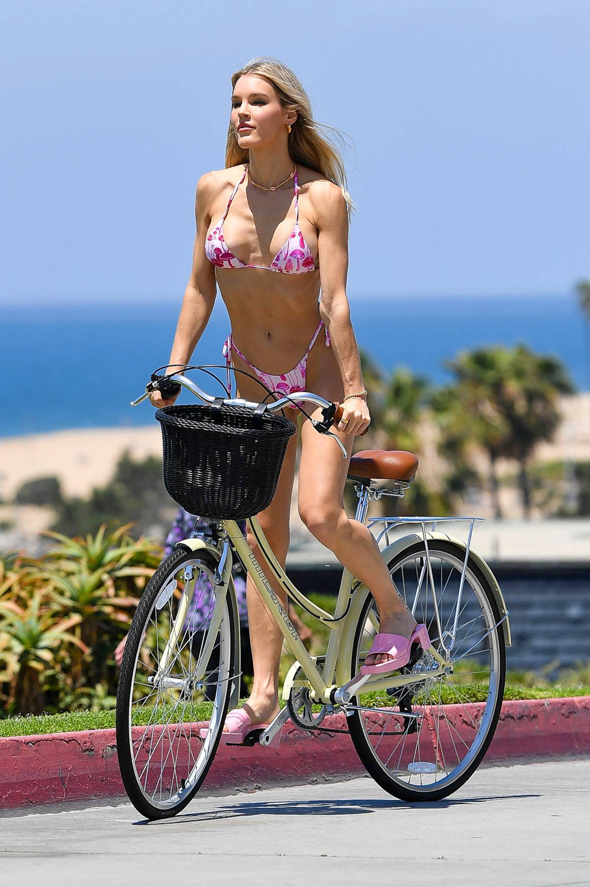 Joy Corrigan stuns in a mushroom print pink bikini while enjoying a bike ride along the beach in Los Angeles