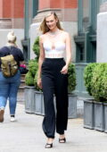 Karlie Kloss looks fashionable in a white corset top and black trousers as she steps out in New York City