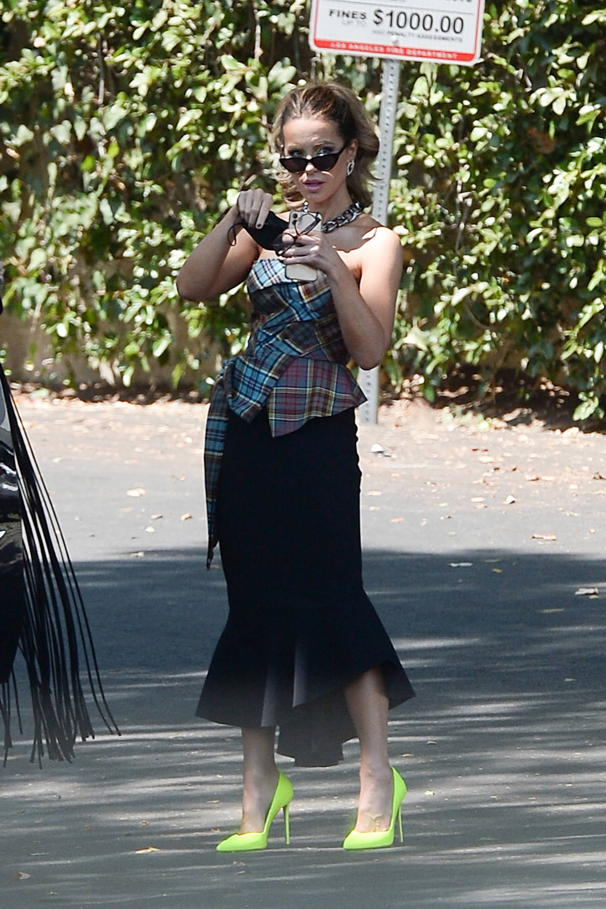Kate Beckinsale looks stylish in a plaid top, black skirt with neon green shoes while heading out in Los Angeles