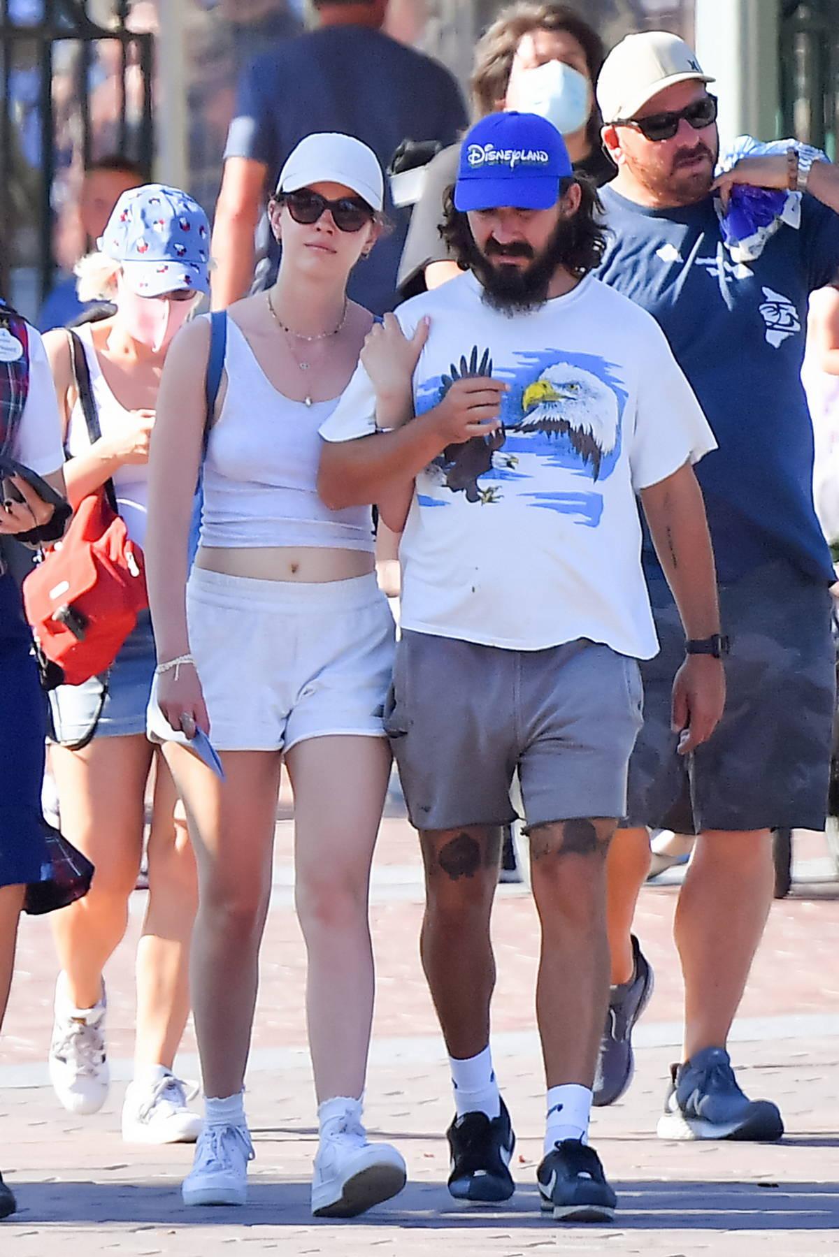Mia Goth and Shia LaBeouf walk arm in arm while enjoying a day at Disneyland in Anaheim, California