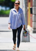 Naomi Watts wears a light blue shirt and navy leggings while out walking her dog in New York City