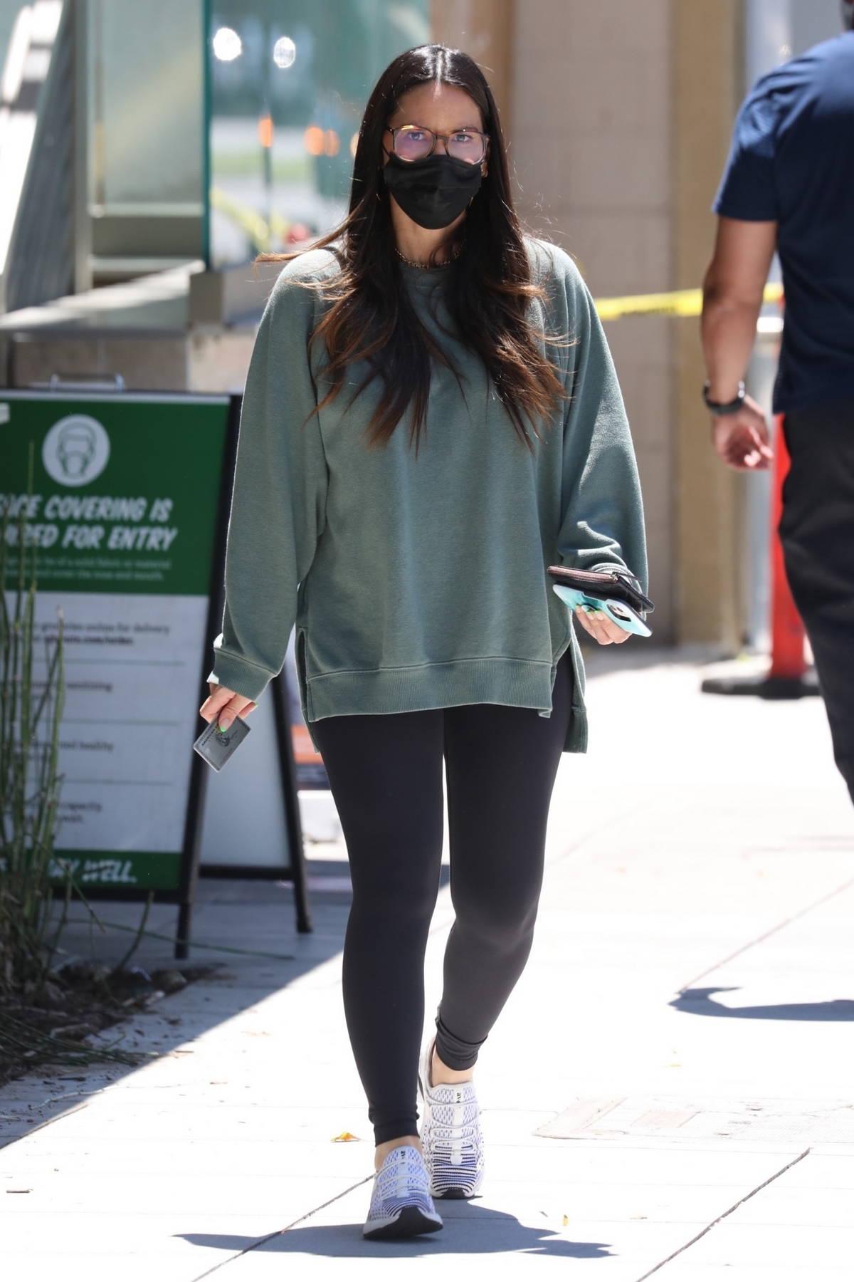 Olivia Munn leaves an office wearing a comfy green sweatshirt and black leggings in Santa Monica, California