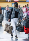 Olivia Wilde stays cozy in sweats paired with a striped scarf and a hat at the JFK Airport in New York City