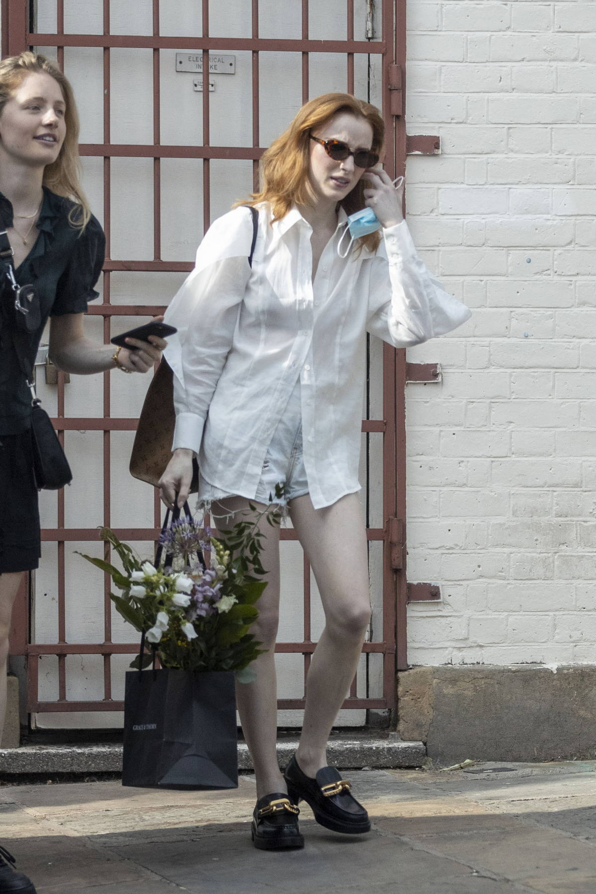 Phoebe Dynevor wears a white shirt and denim cutoffs as she leaves a photoshoot in London, UK