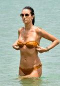 Alessandra Ambrosio displays her beach body in an orange bikini as she cools off in the sea in Florinópolis, Brazil