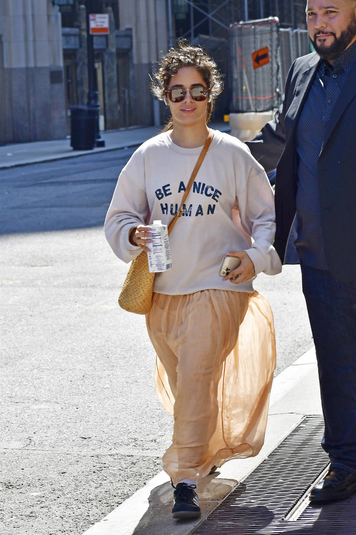 Camila Cabello wears a 'Be A Nice Human' sweatshirt and peach skirt while out in New York City