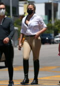 Chrissy Teigen rocks a white shirt and a pair of beige jodhpurs with knee-high boots while stepping out in Los Angeles