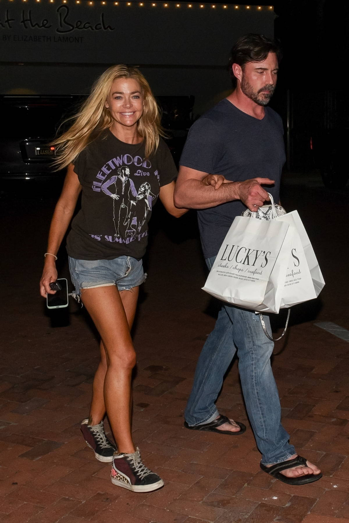 Denise Richards and husband Aaron Phypers walk arm in arm as they leave after dinner with her daughter in Malibu, California