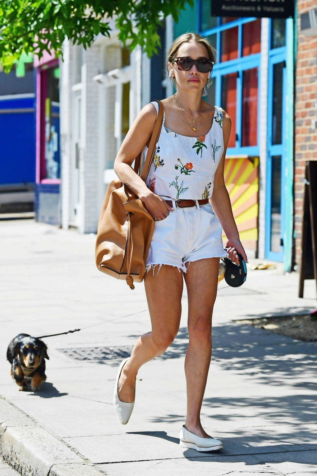 Emilia Clarke wears a floral print top and denim shorts as she takes her pooch to a dog park in London, UK