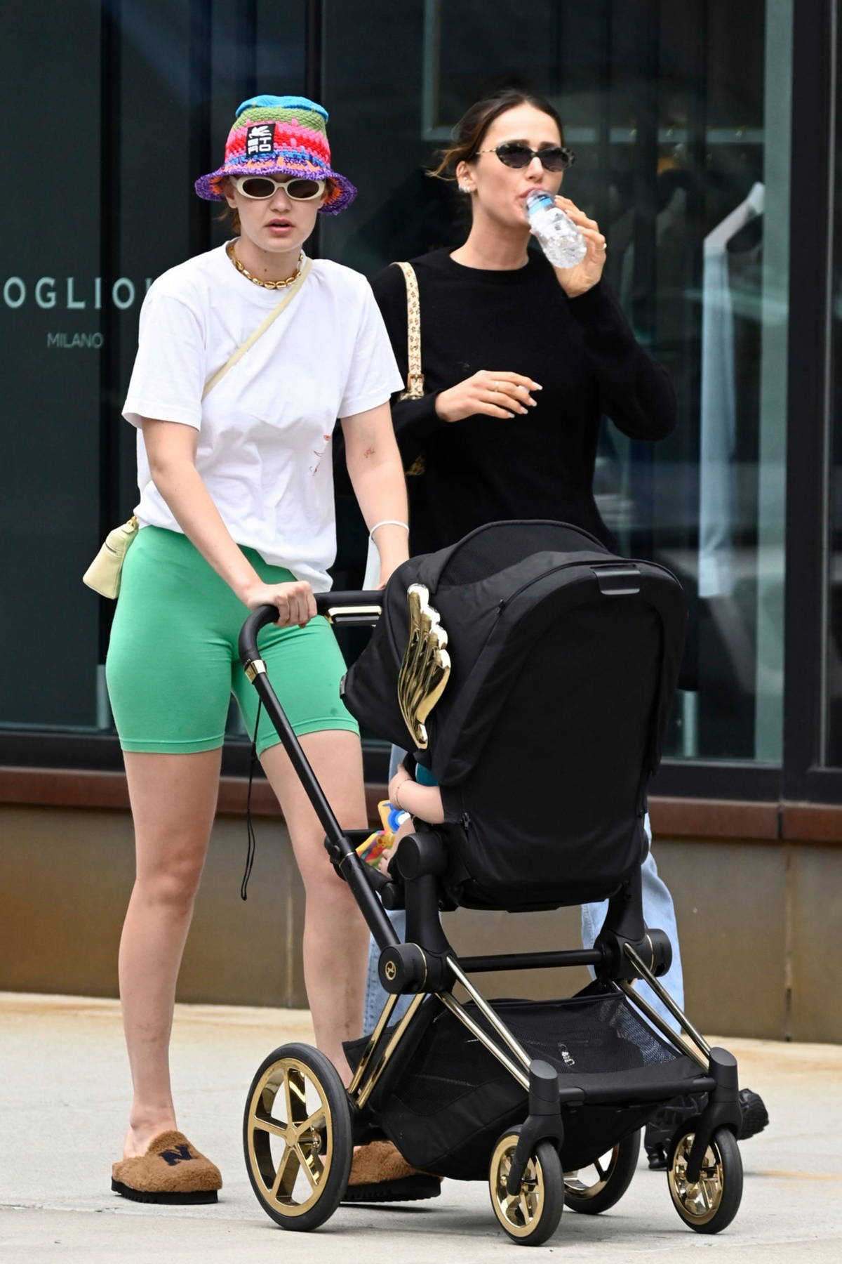 Gigi Hadid wears a white tee and green legging shorts while out for stroll with her daughter in SoHo, New York City