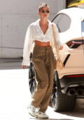 Hailey Bieber looks chic in pleated pants and a white crop top while heading to a meeting in Beverly Hills, California